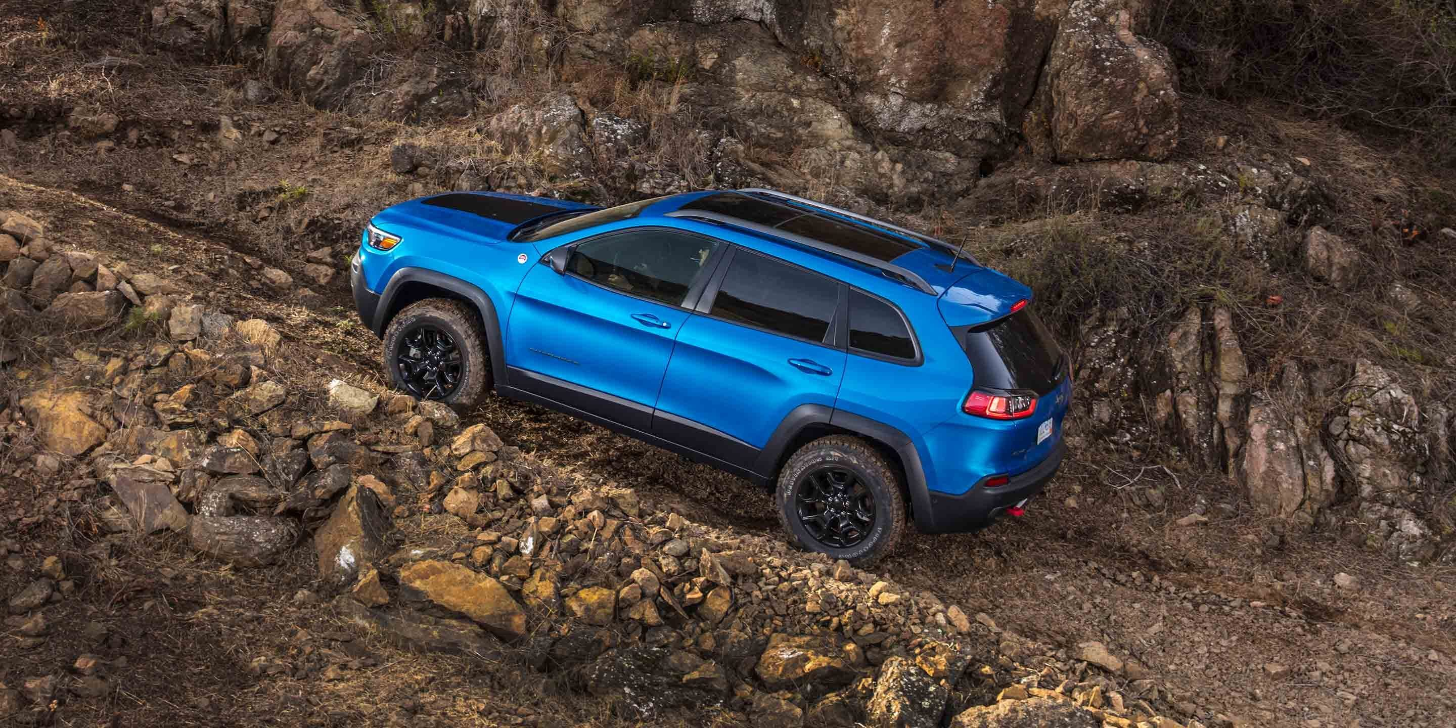 blue 2019 jeep cherokee driving up a steep dirt and rock path