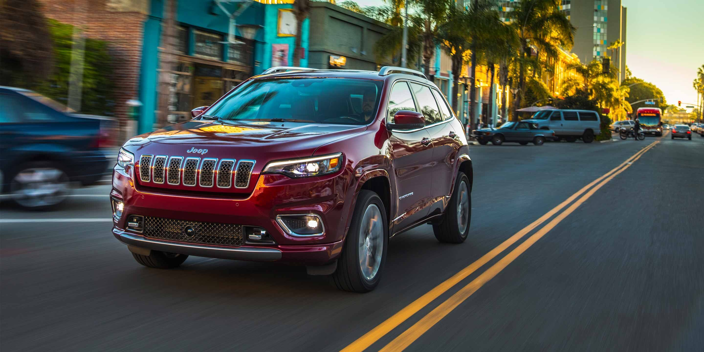 red 2019 jeep cherokee driving through the city
