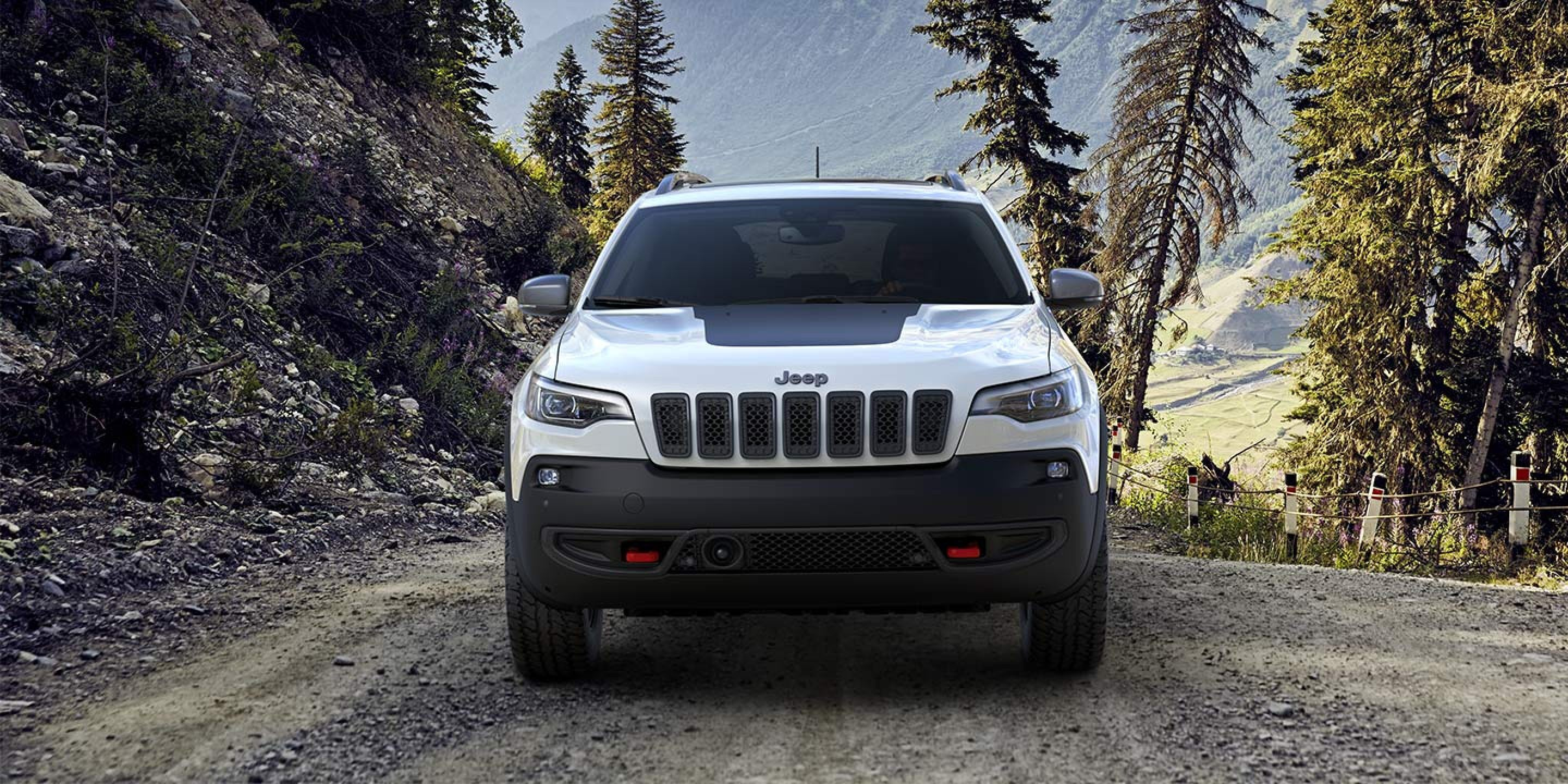 white 2019 jeep cherokee driving on a dirt path