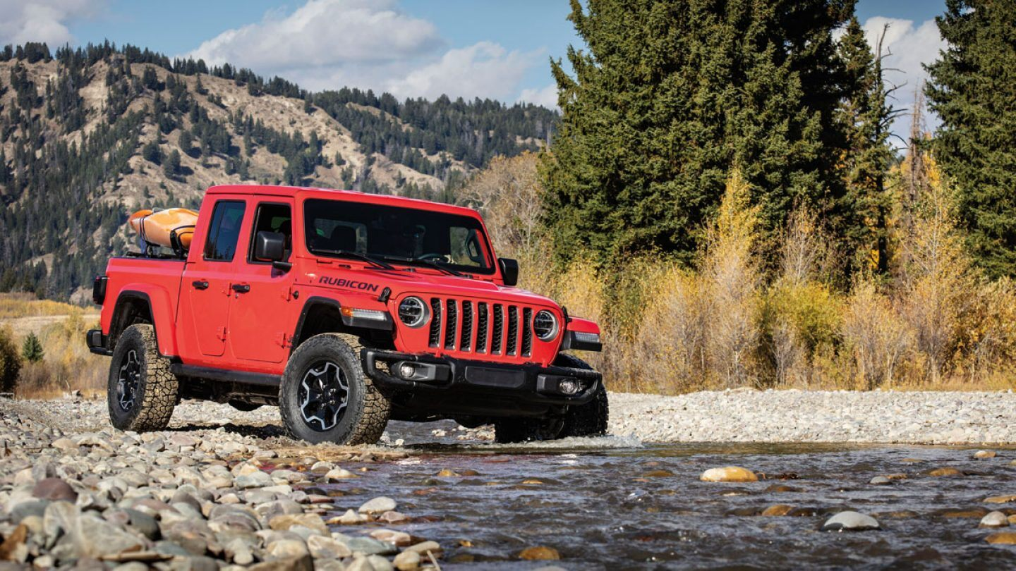 red 2020 jeep gladiator offroading on rocks and water