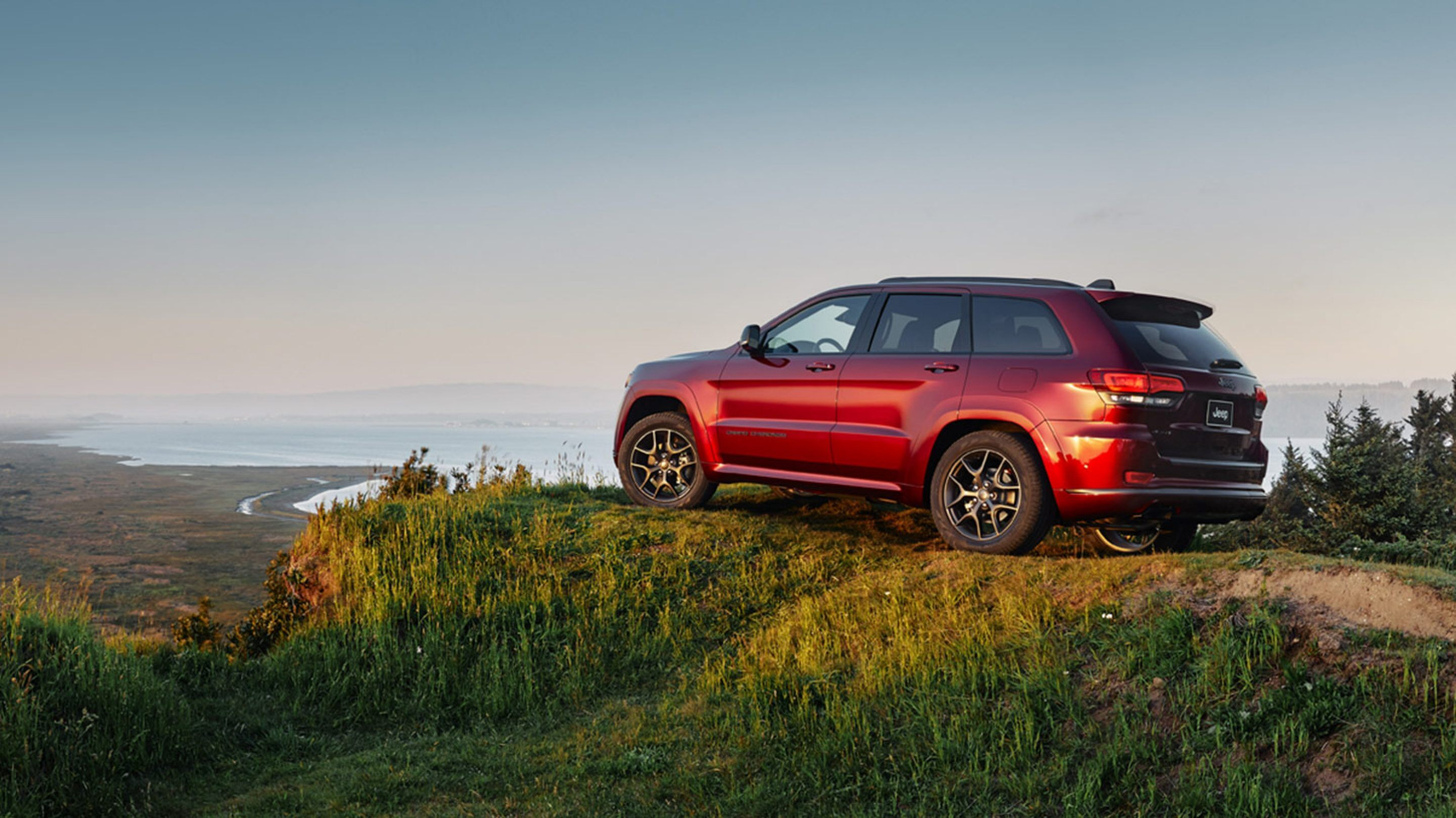 red 2019 jeep grand cherokee parked on a mountain