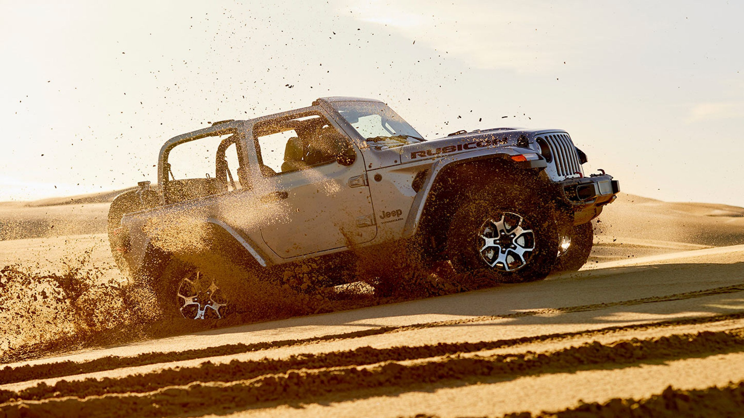white 2020 jeep wrangler driving in sand