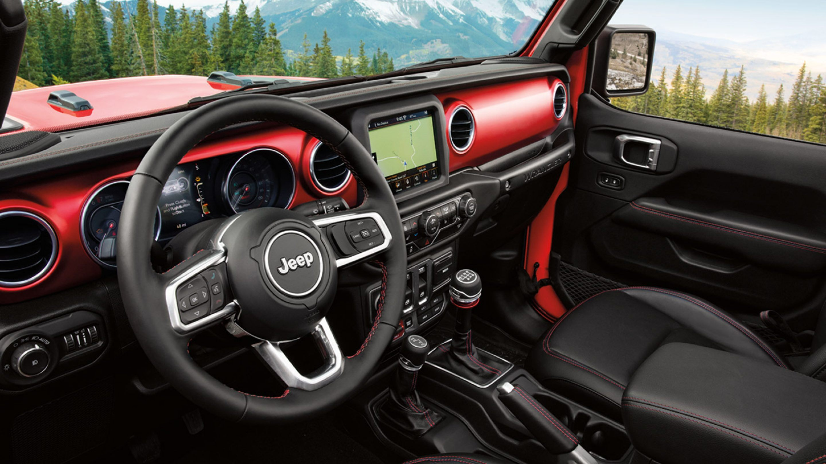 interior of a red 2020 jeep wrangler parked on a mountaintop