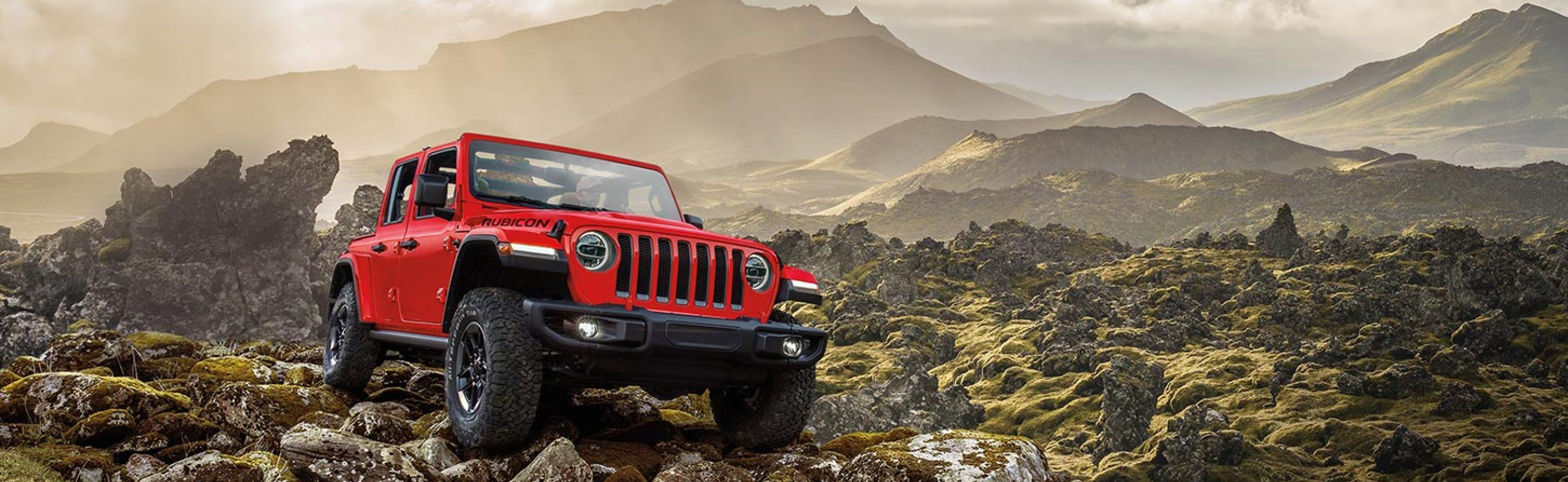 red 2020 jeep wrangler parked on rocks on a mountain