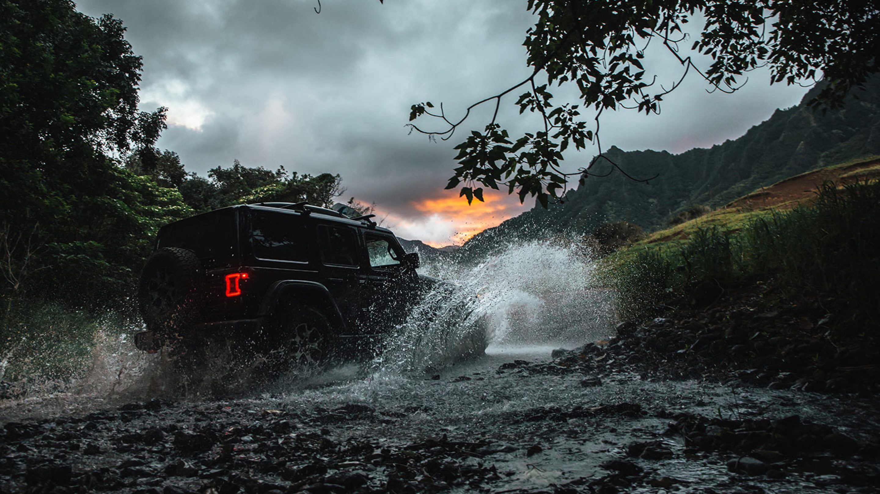 black 2020 jeep wrangler driving through river at sunset