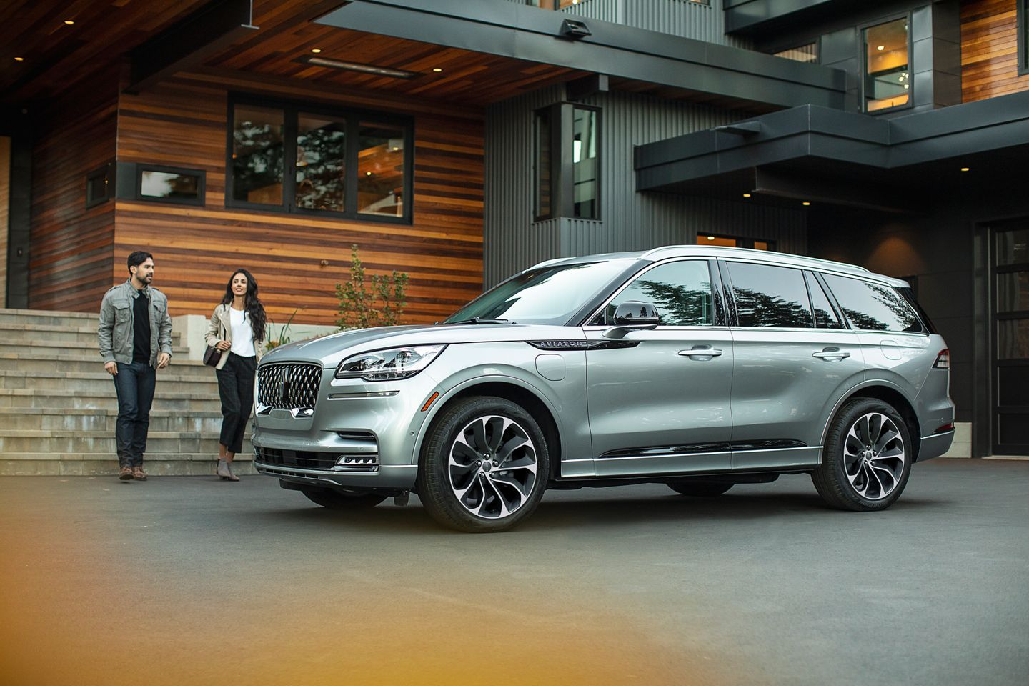 couple walking towards a silver 2019 lincoln aviator