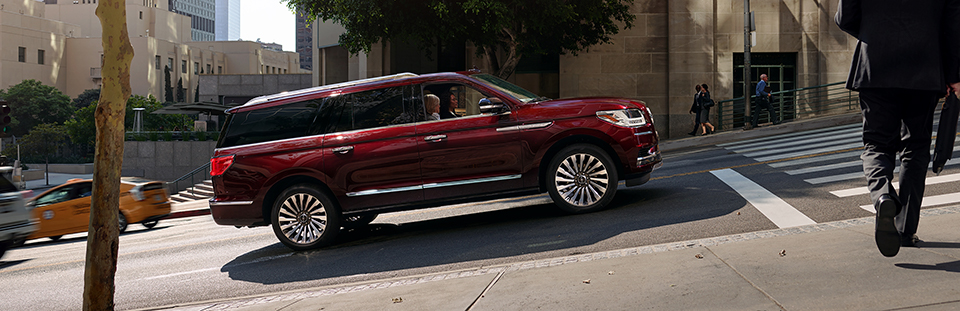red 2019 lincoln navigator driving on a city street