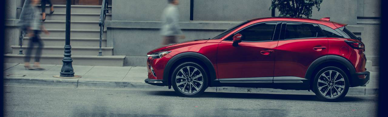 red 2019 mazda cx-3 parked on a city street as people walk by
