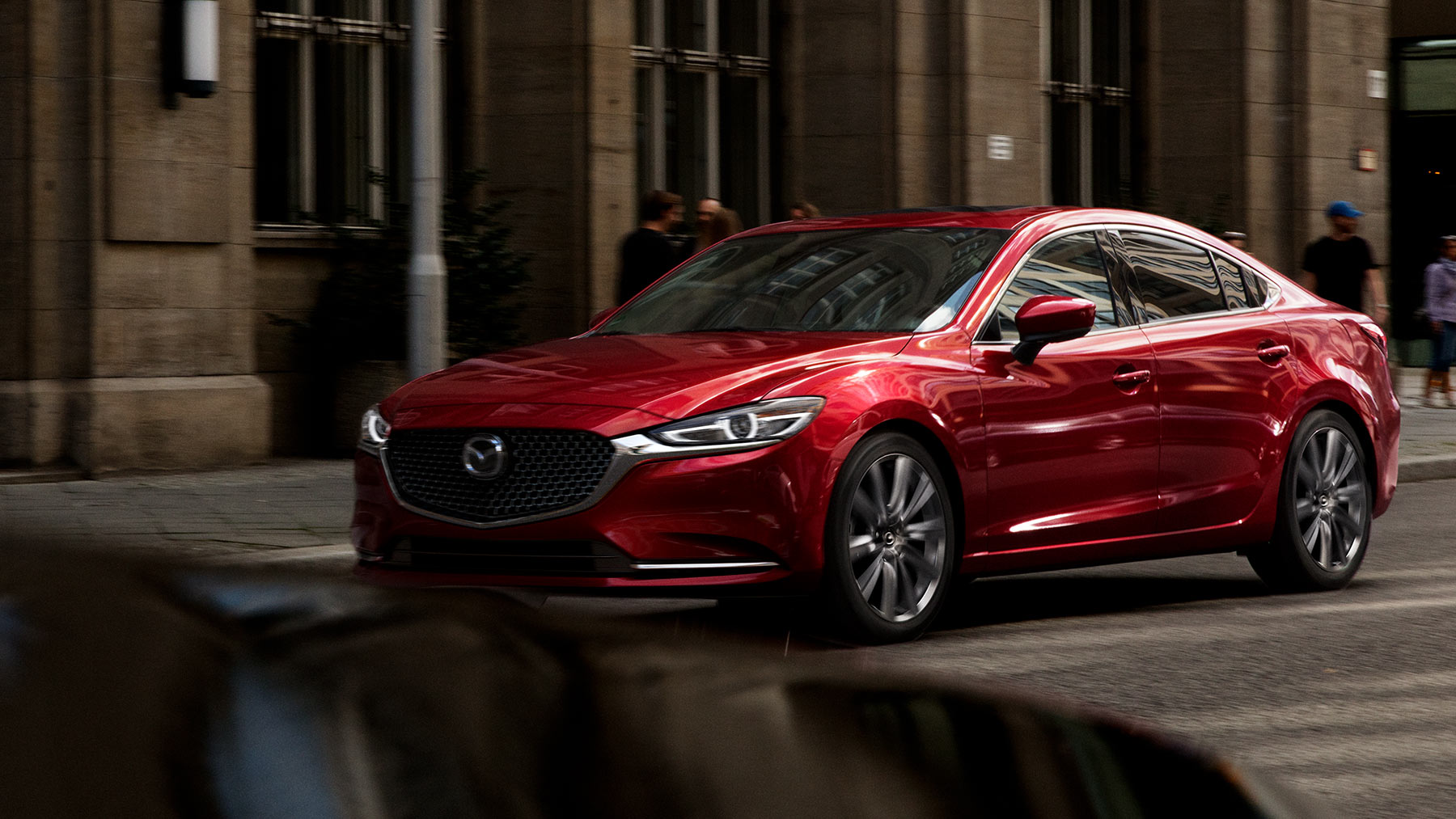 red 2018 mazda6 driving through the city