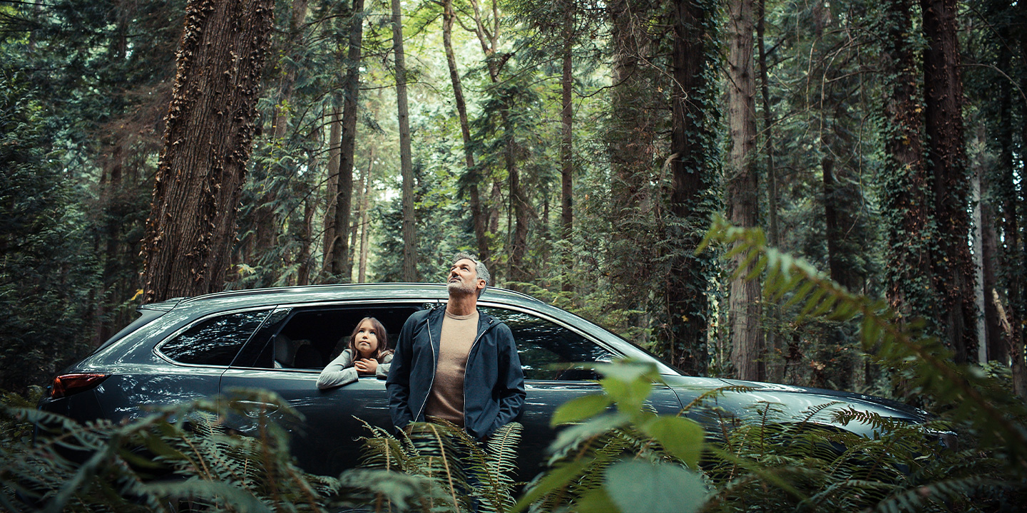 father and daughter enjoying a beautiful forest in their 2020 mazda cx-9