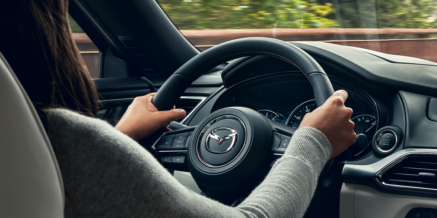 person gripping steering wheel of a 2020 mazda cx-9