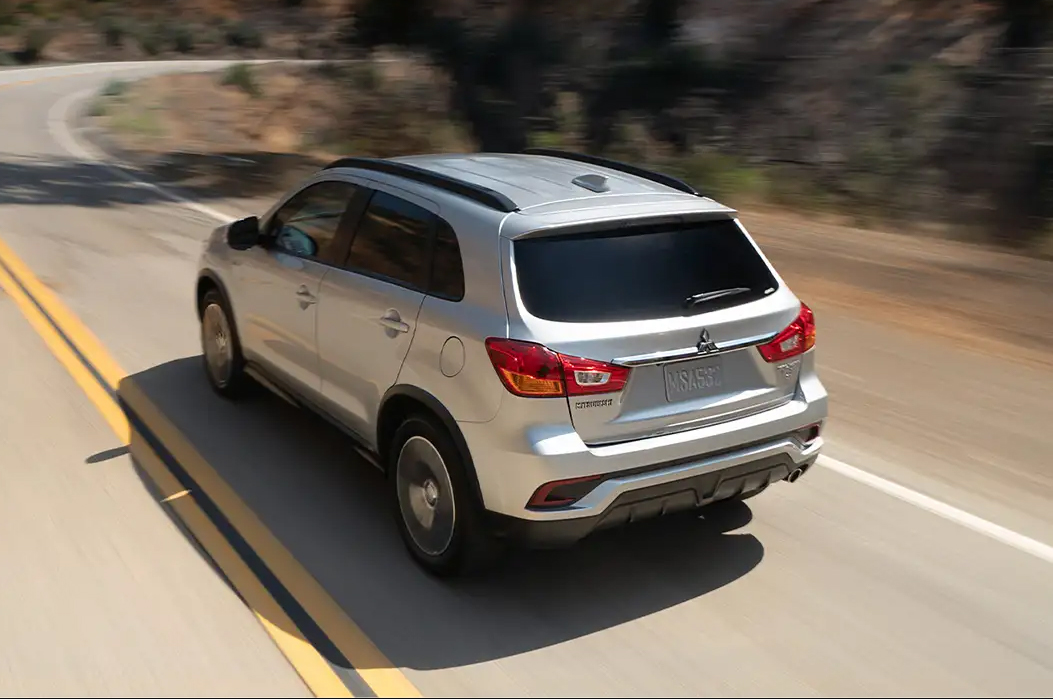 back of silver 2019 mitsubishi outlander sport driving fast