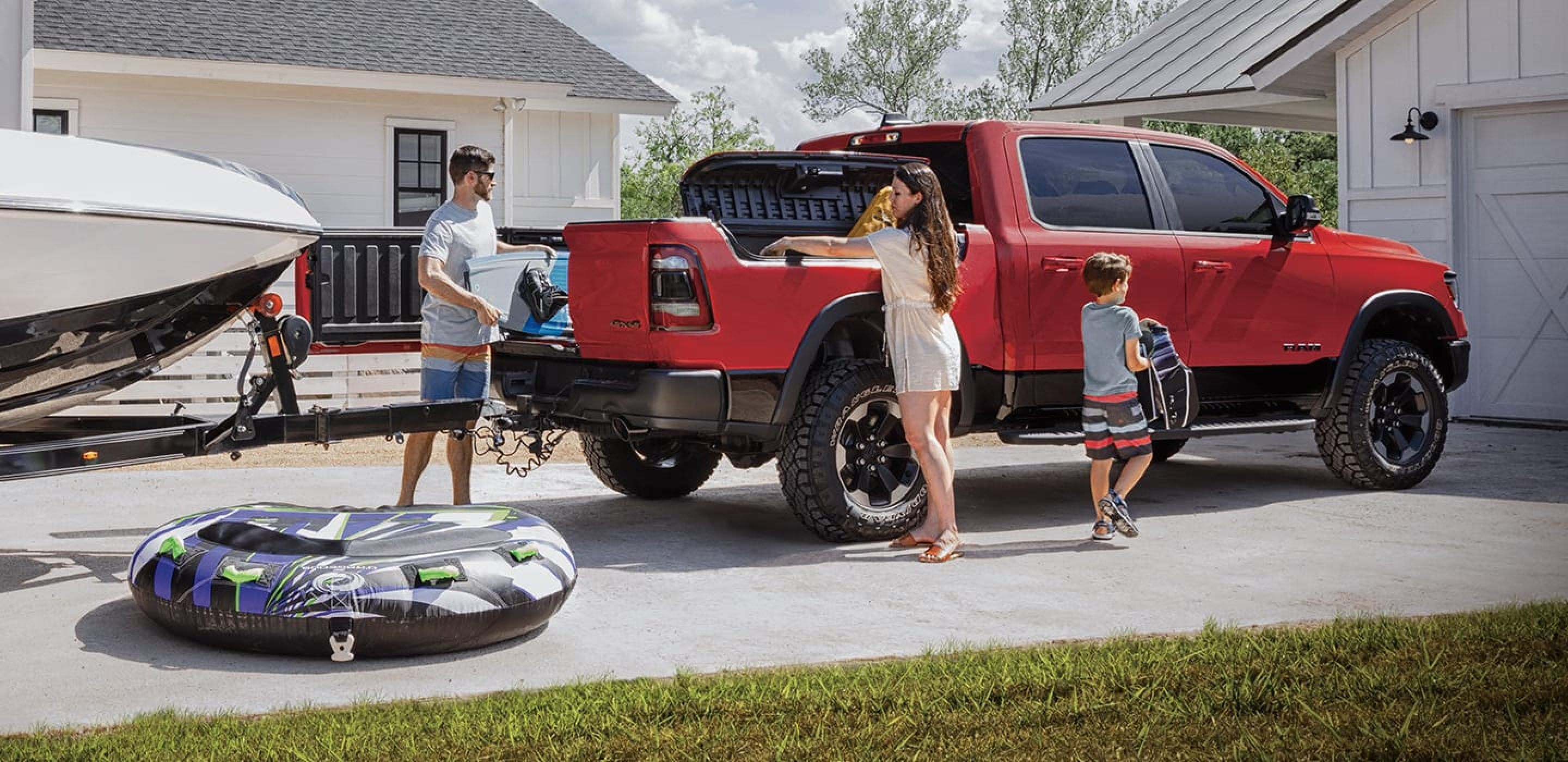 family loading up a red 2020 ram 1500 with gear for a day out on the lake
