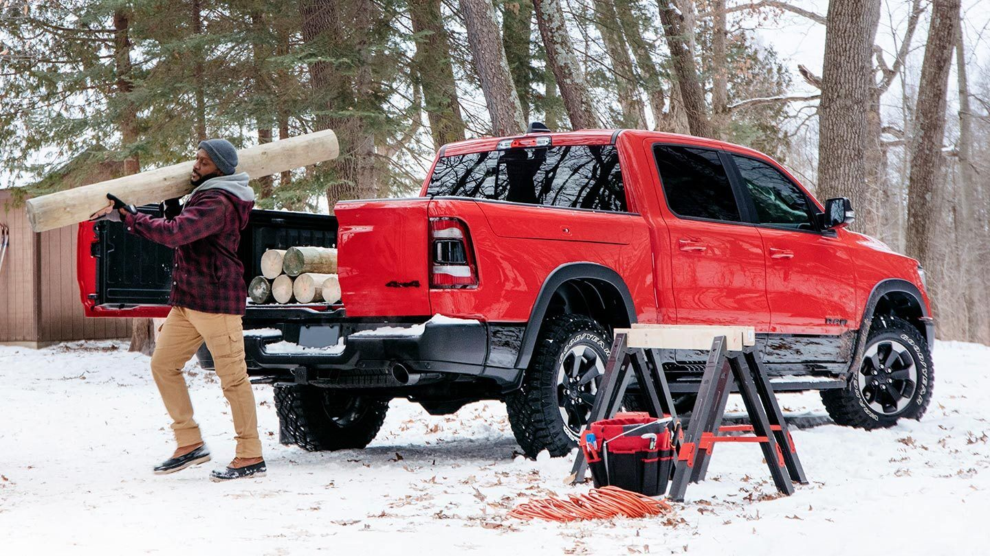 man carrying wood out of his red all-new 2019 ram 1500