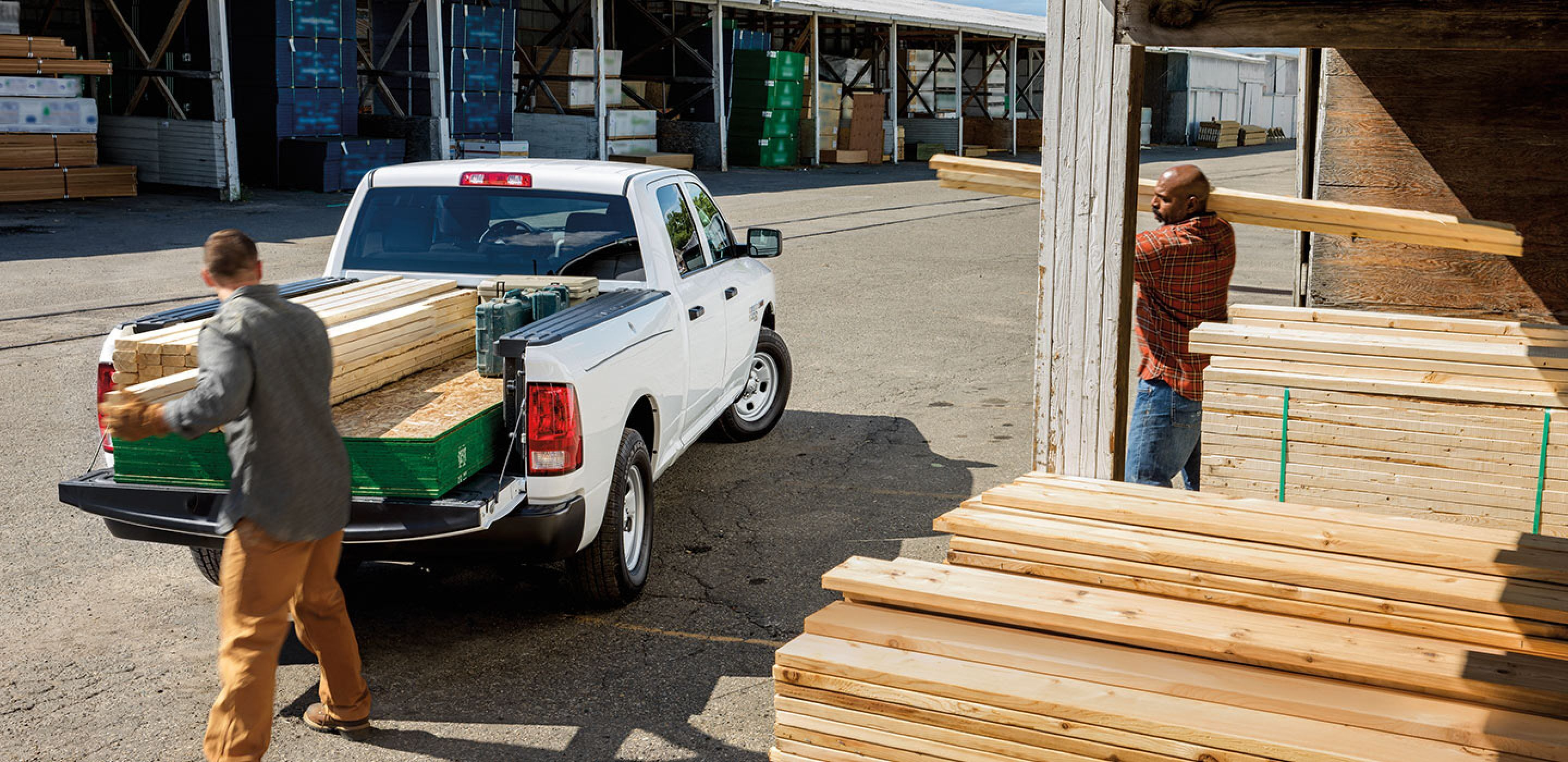 white 2019 ram 1500 being loaded with wood
