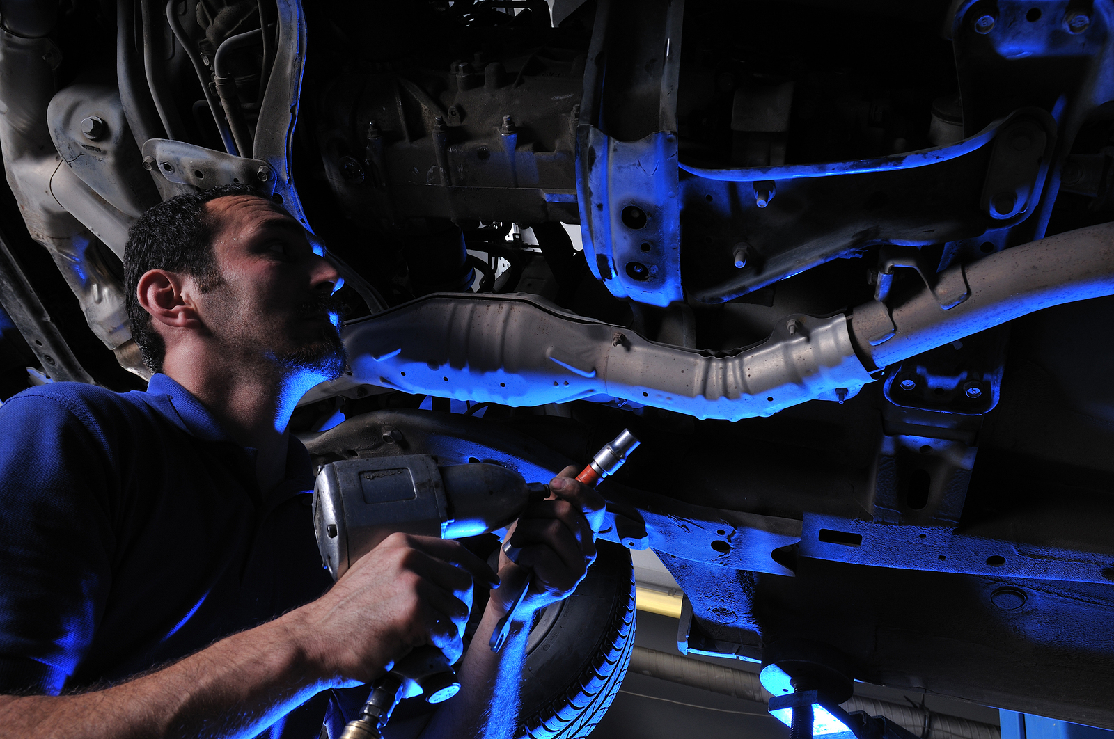 mechanic working on transmission of a vehicle