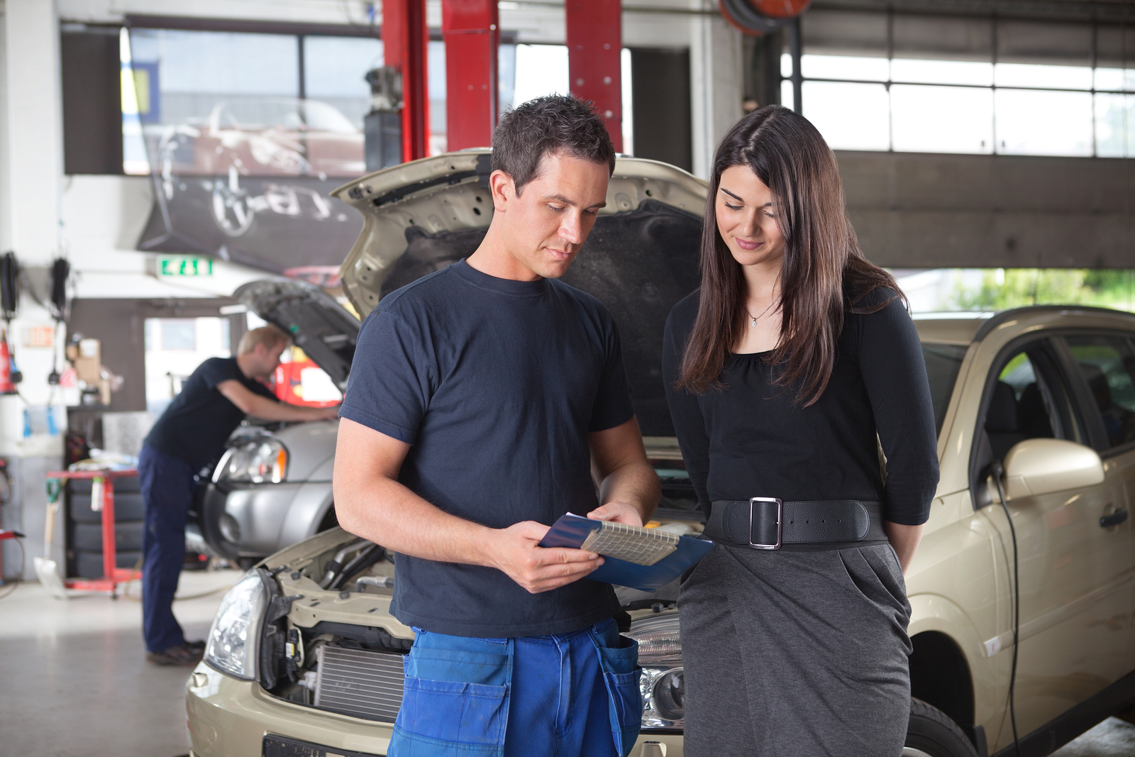 mechanic showing a customer a breakdown of the repairs they did to her vehicle