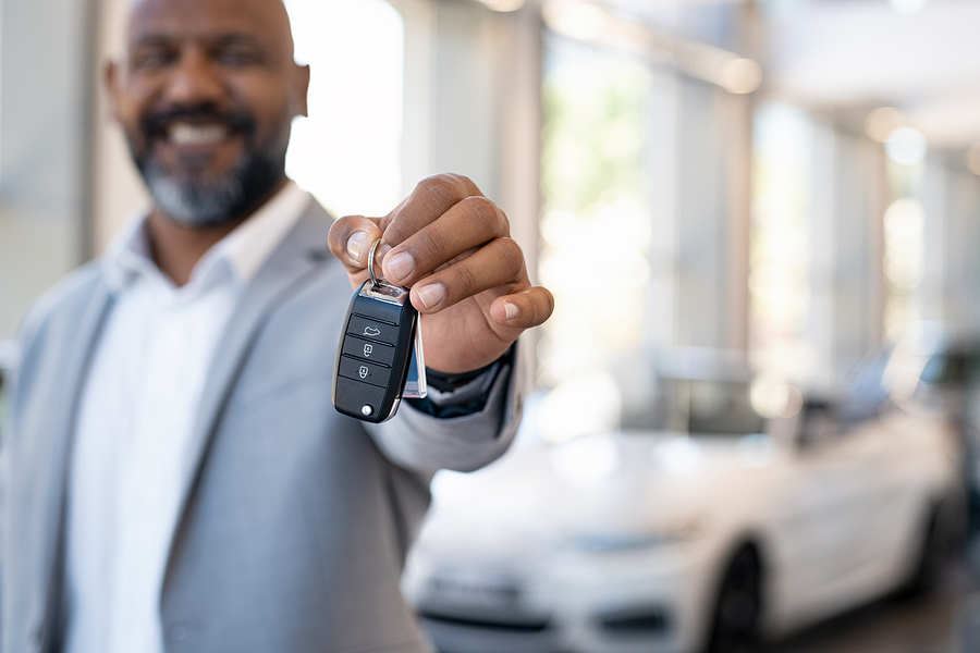 smiling man handing keys to brand new vehicle