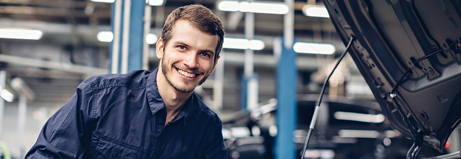 smiling mechanic working in the engine bay of a vehicle