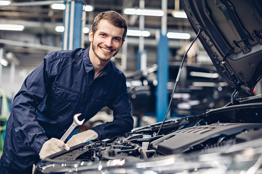 smiling mechanic working on car engine