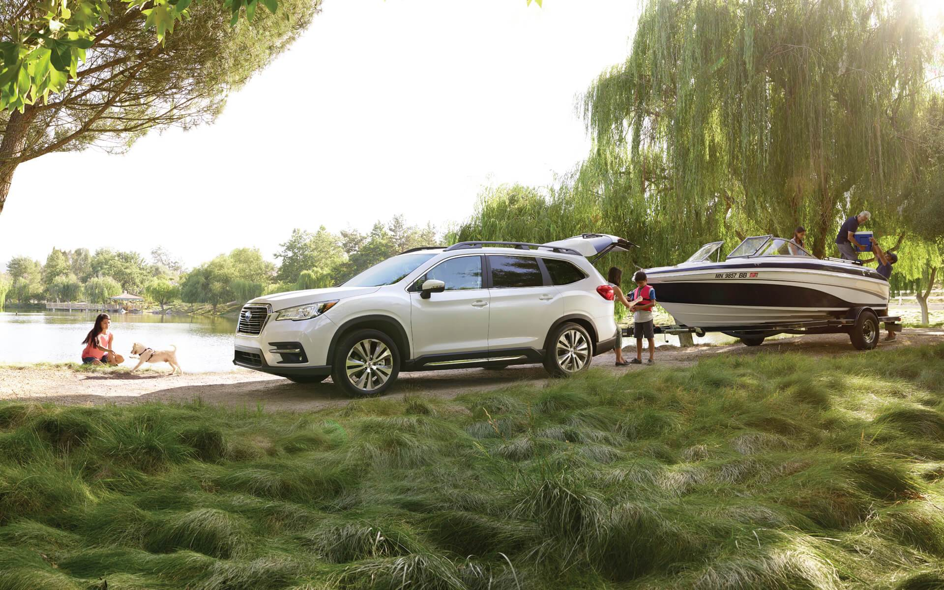 white 2020 subaru ascent towing a boat at a lake
