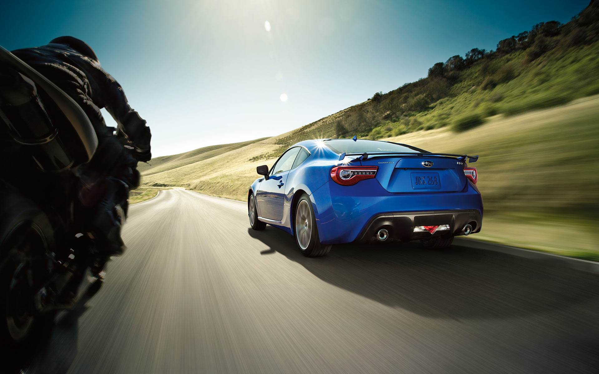 blue brz driving alongside a motorcycle