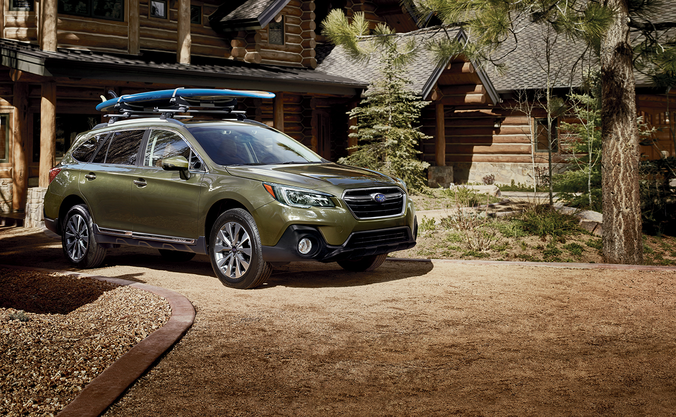 A green 2019 Subaru Forester is parked in front of a wooden home in the forest.