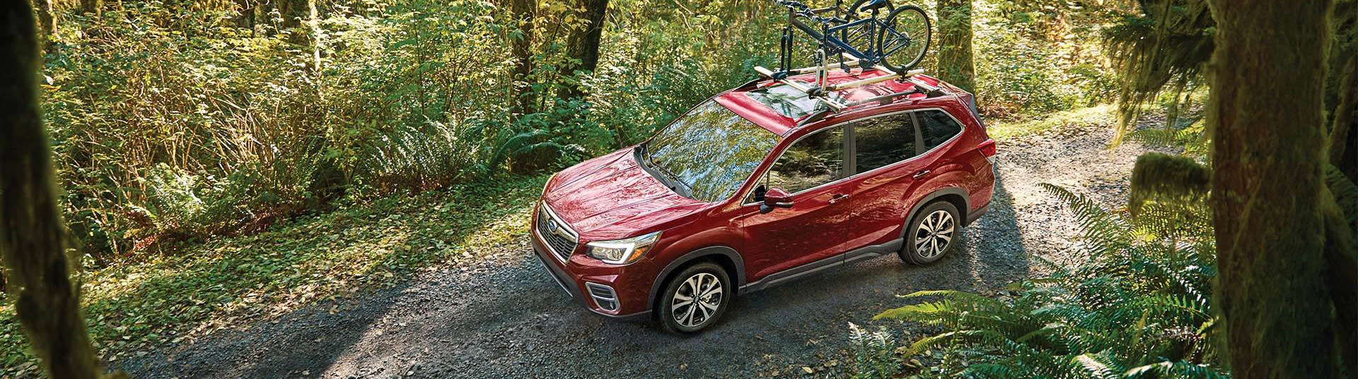 red 2020 subaru forester driving through the woods