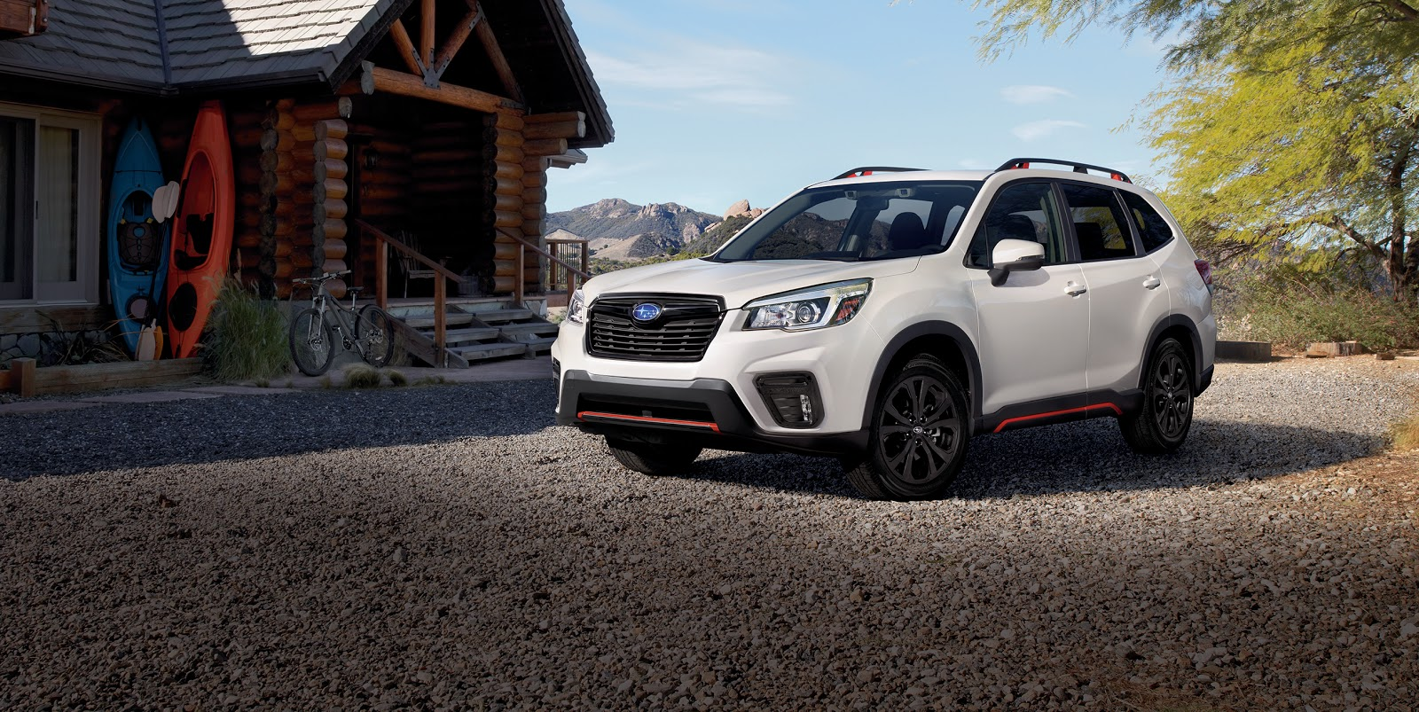 white subaru forester parked in front of a cabin