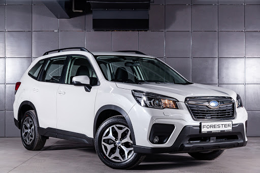 white subaru forester parked in front of grey tiles