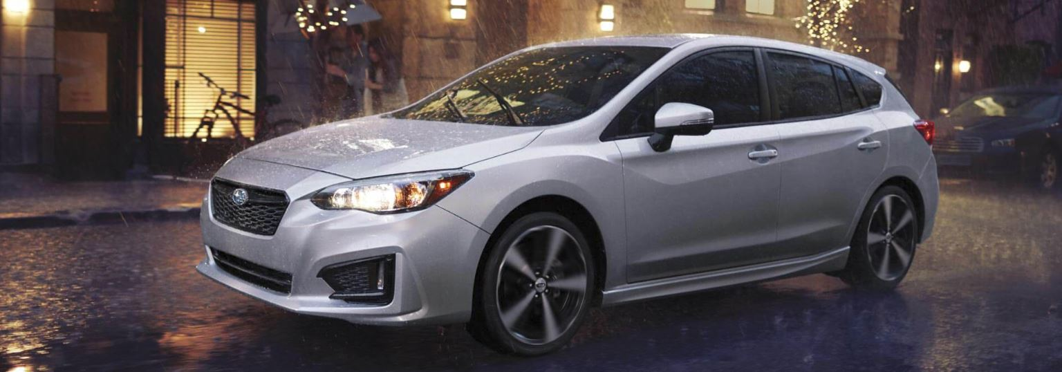 white 2019 subaru impreza hatchback driving in the rain