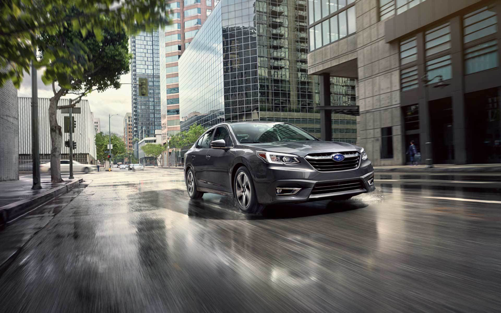 magnetite gray metallic 2020 subaru legacy driving through the city after rain