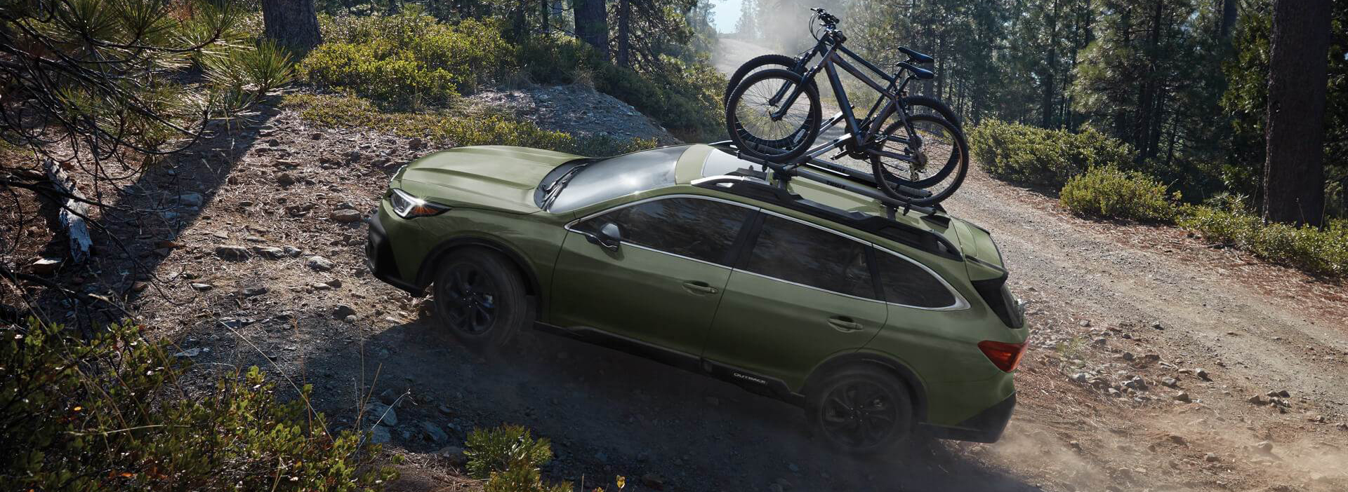 green 2020 subaru outback driving on a dirtpath with bikes on a bike rack
