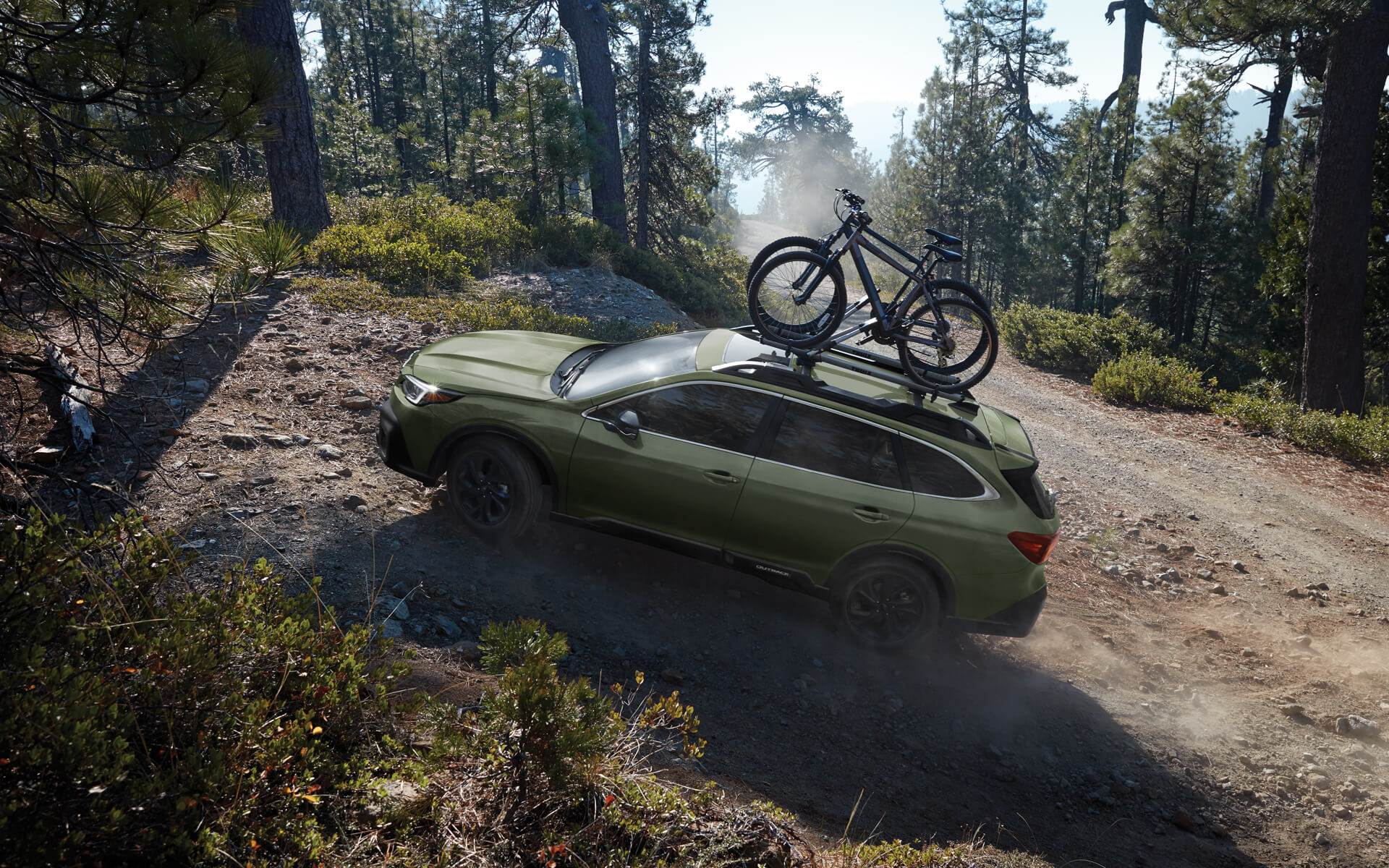 autumn green metallic 2020 subaru outback parked on a dirt path with bikes on a roof rack