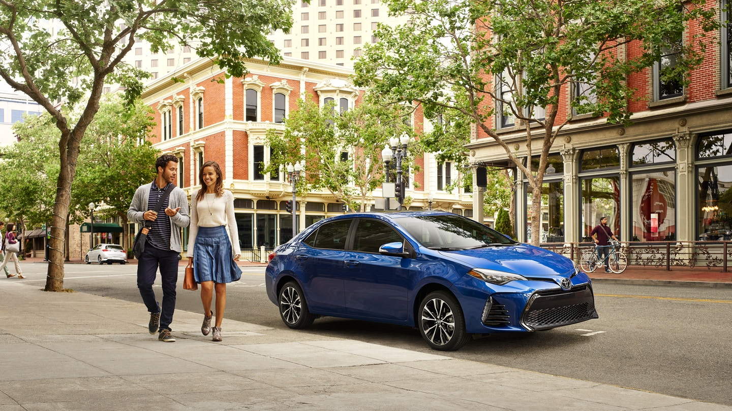 Couple walking away from Blue 2019 Toyota Corolla