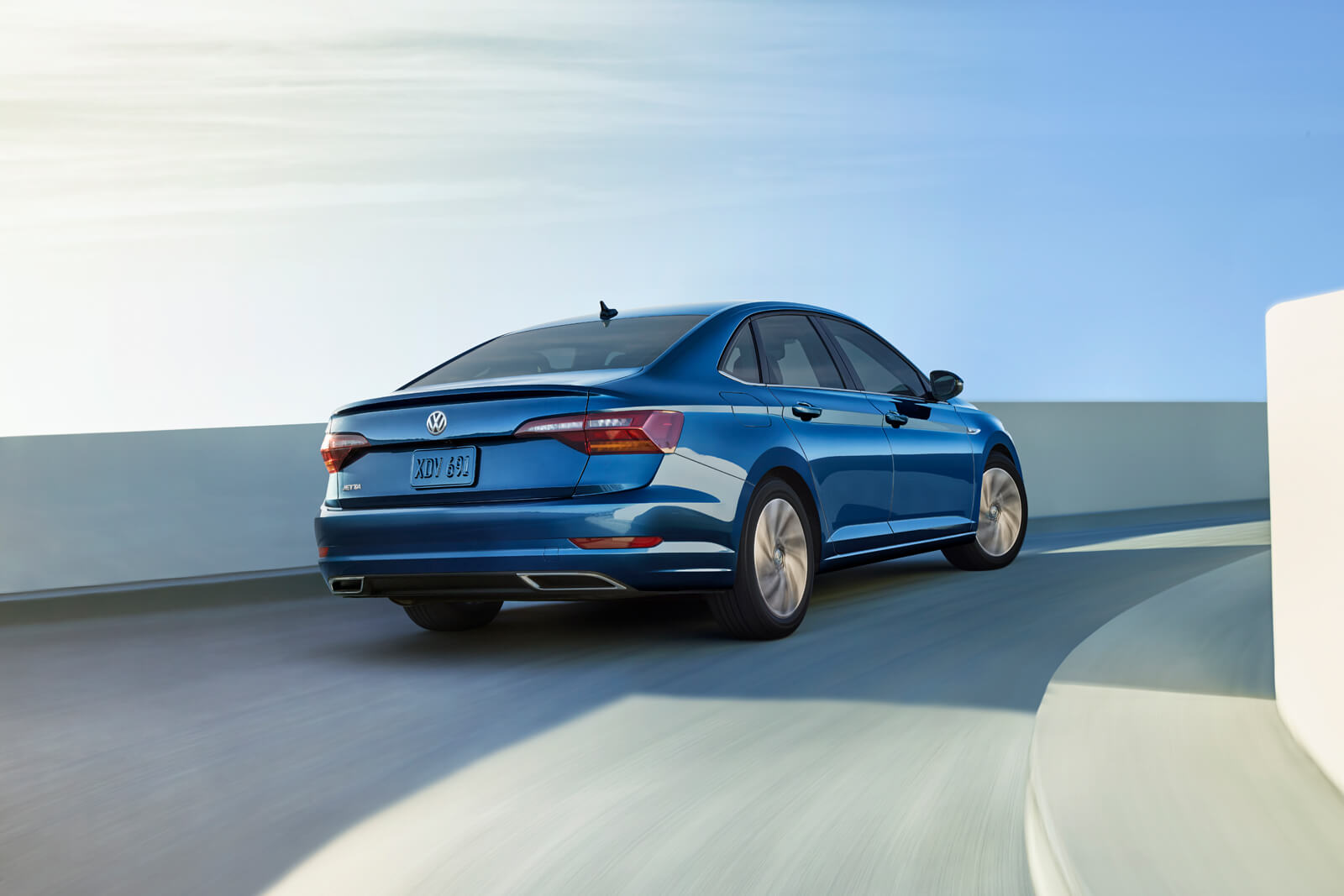 blue 2019 volkswage jetta driving up a ramp