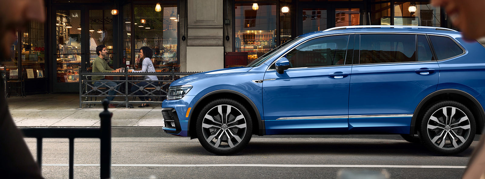 blue 2020 volkswagen tiguan parked on a street in front of a restaurant