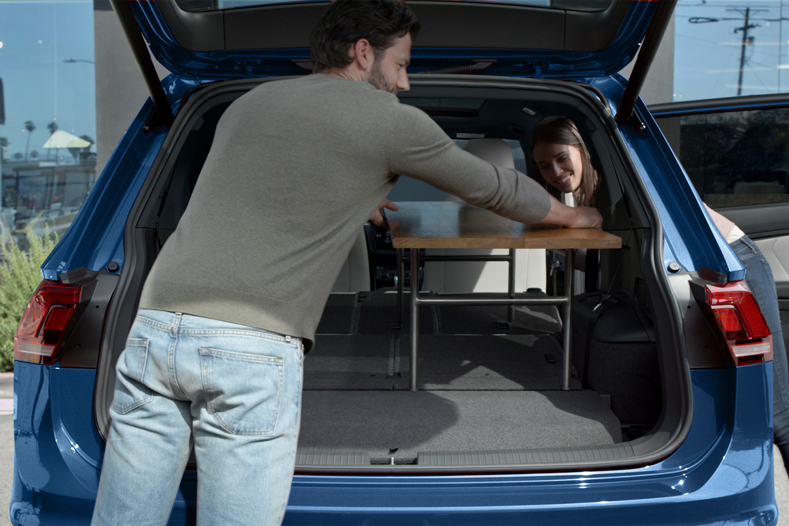 couple loading table into the back of a blue 2020 volkswagen tiguan