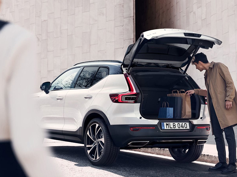 man putting bags into the back of a volvo