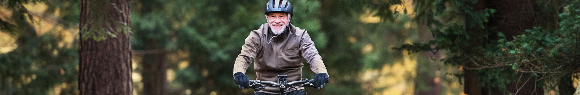 A senior man biking on a forested path in the fall