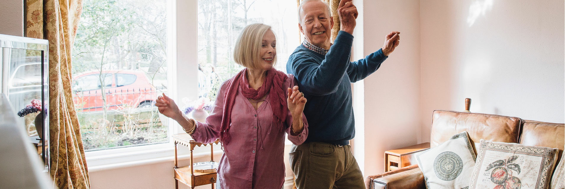 An elderly couple dancing to music in their home