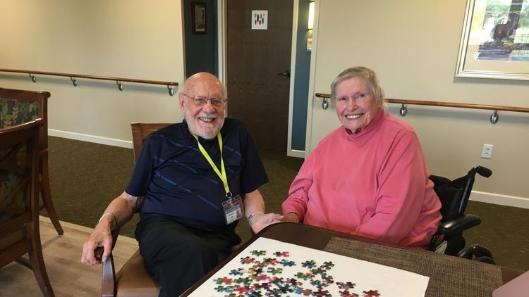 Two seniors pose for a photo in front of puzzle pieces