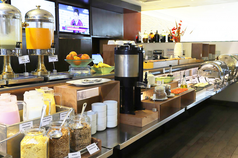 The breakfast buffet is shown to be stocked full of fresh juices, pastries, and local treats.