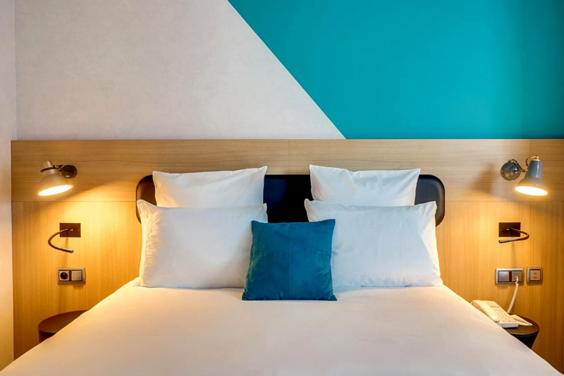 A bed with white linens and a colorful wall behind it.