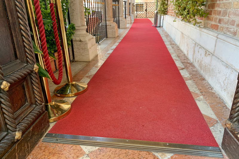 Exterior entrance with red carpet and double doors
