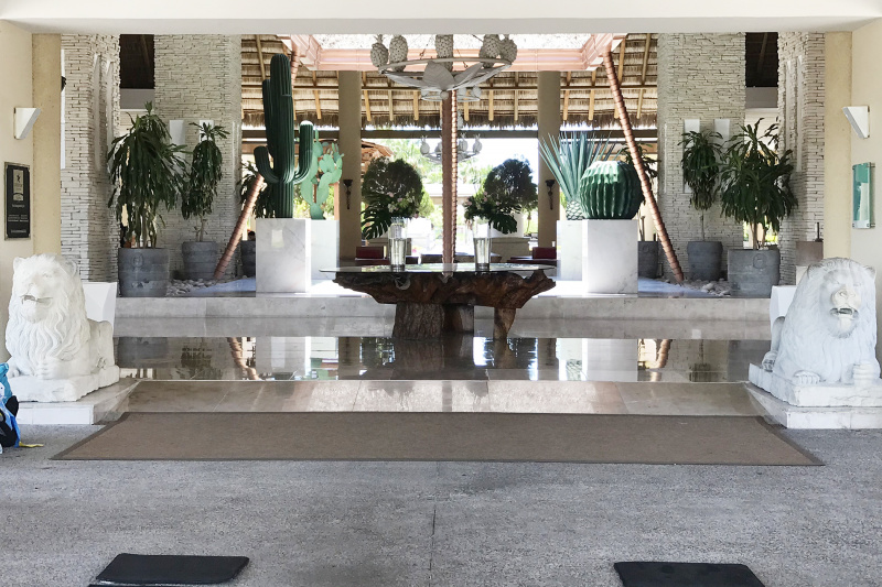 Lobby and entryway with large, livewood table, statues, and a ramp.