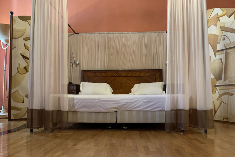 Junior room has a queen sized bed, two bedside tables and lamps