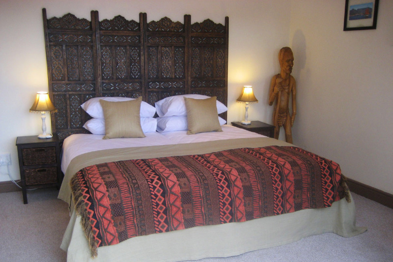 Molo room includes a large spacious bed, bedside lamps, and tables, and a rustic wooden headboard