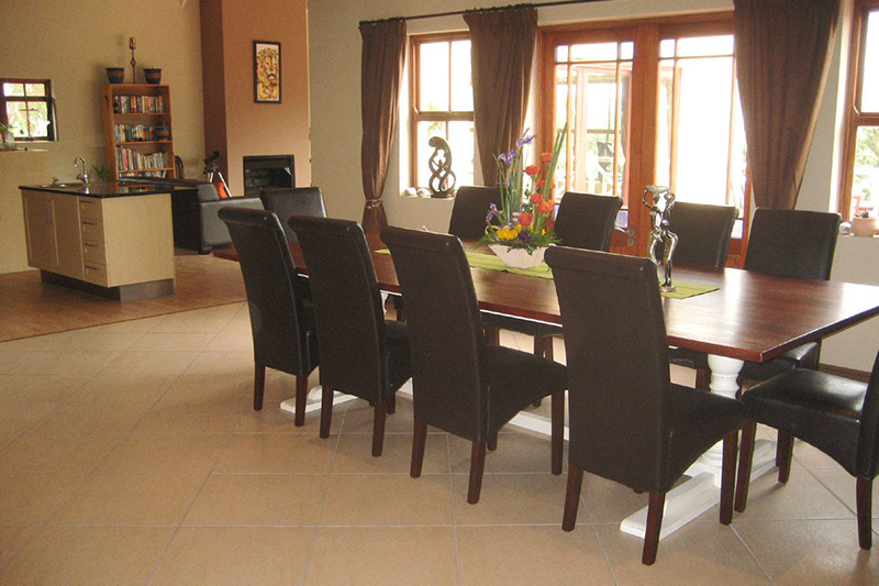 The dining room connects to a communal living room with comfortable couches