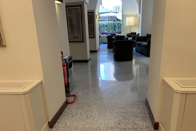 The corridor in the lobby has granite flooring, a comfortable seating area, and floor to ceiling windows